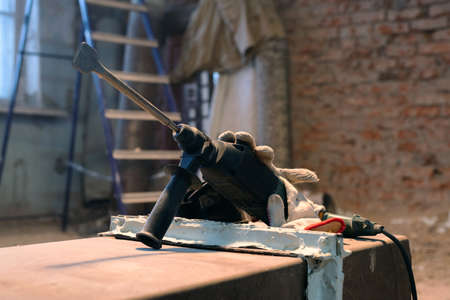 Hammer drill with chisel close up on the old brick wall background. 版權商用圖片