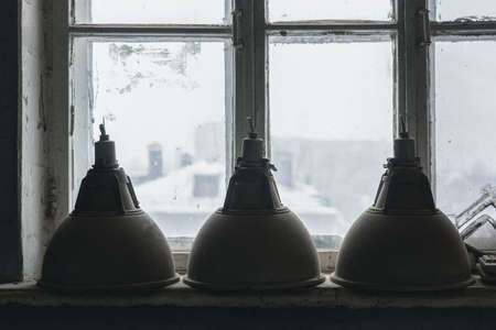 Old industrial ceiling lamps on the window sill close up background.