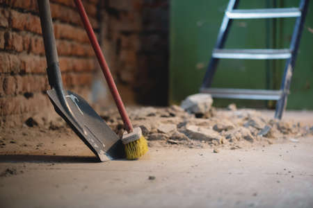 Shovel and broom on the dusty construction site floor background. 版權商用圖片