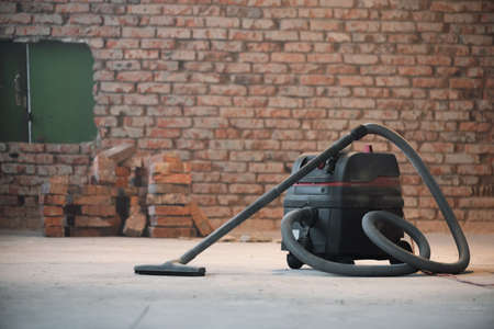 Industrial vacuum cleaner on the dusty floor of construction site. 版權商用圖片