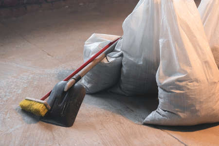 Shovel, broom and bags with a construction garbage on the dusty construction site floor background.