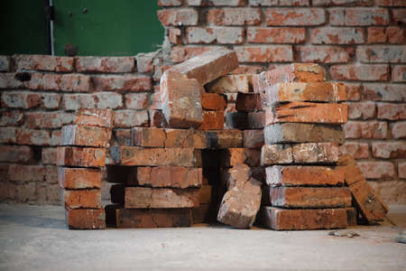 Stack of old bricks on the brick wall background.