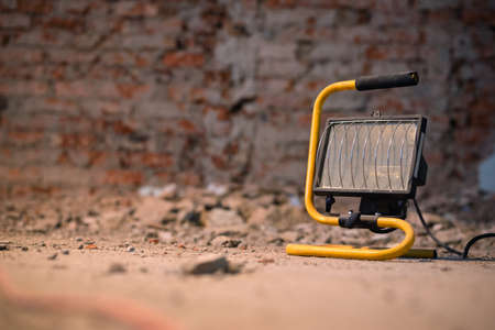 Spotlight close up on the dirty floor of construction site on the old brick wall background. 版權商用圖片