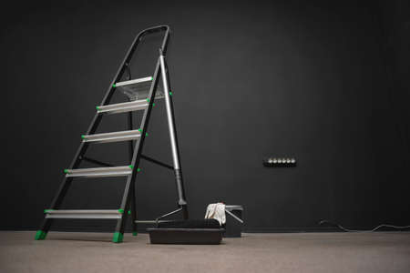 Paint roller, step ladder and paint on a black wall background with copy space.