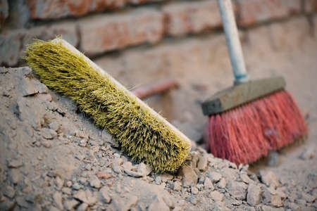 Broom on the dusty construction site floor background.