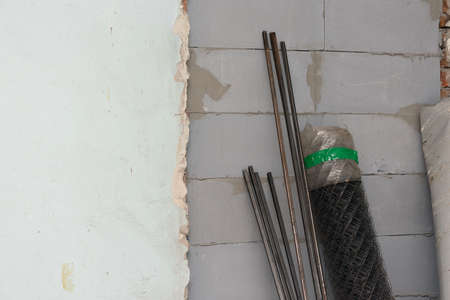 Profile pipe and netting roll on the old wall background.