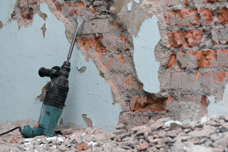 Hammer drill with chisel on the old brick wall background. Removing an old putty from the wall background. 版權商用圖片