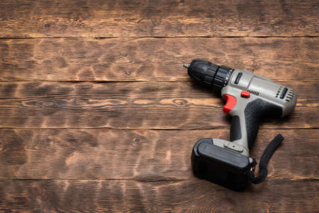 Cordless screwdriver on the wooden workbench background with copy space.