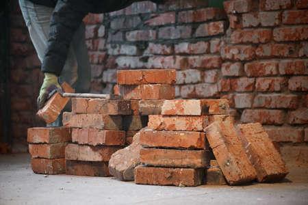 Bricklayer is laying a brick close up.