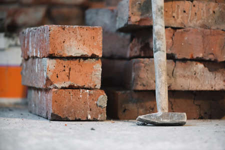 Stack of old bricks and hammer on the brick wall background.