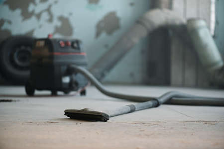 Blurred industrial vacuum cleaner on the dusty floor of construction site.