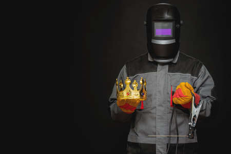 Welder man in the helmet with a welding terminals is holding in the hand a golden crown on the black background. Best welder concept.