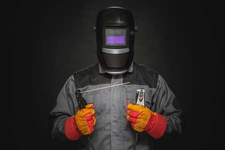 Welder man in the helmet with a welding terminals on the black background.