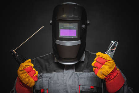 A welder in a helmet with a welding terminals in hand on a black background.