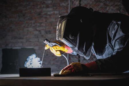 Welder is welding a metal pipe on the workbench. 版權商用圖片