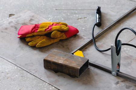 Welding gloves and metal frame on the floor background.