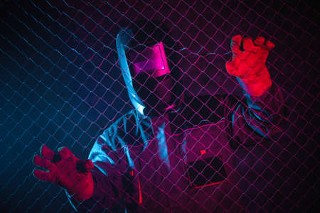 Welder in the neon lights in the welding helmet.