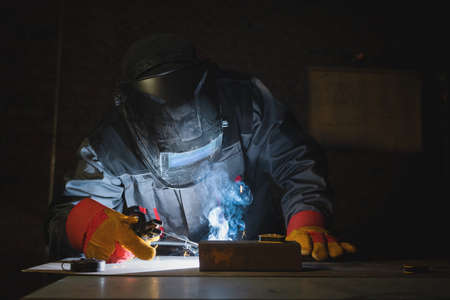 Welder is welding a metal pipes on the workbench in the dark. Фото со стока