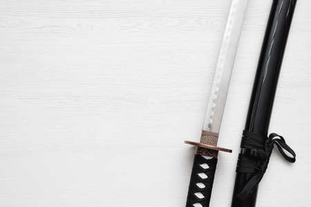 Katana sword on the white wooden table background with copy space.