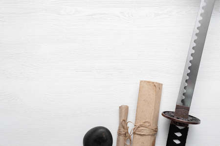 Katana sword and ancient paper scroll on the white wooden table background with copy space. Фото со стока