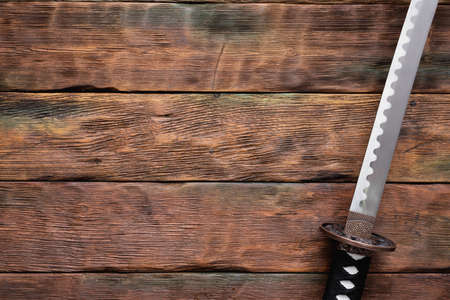 Katana sword on the brown wooden table background with copy space.