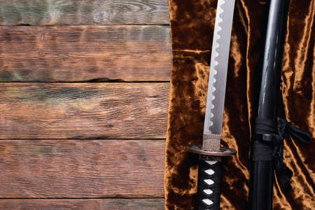 Katana sword on the golden cloth on the brown wooden table background with copy space.