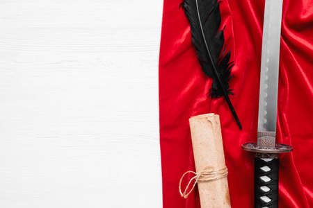 Katana sword, feather pen and ancient paper scroll on the red cloth on the white wooden table background with copy space. Фото со стока