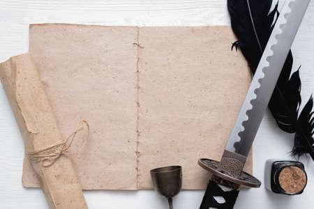 Katana sword, blank page book with copy space and ancient paper scroll on the white wooden table background. Book of fighting techniques concept.