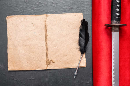 Samurai story book template. Katana sword on the red cloth and blank page book with copy space on the table. Фото со стока