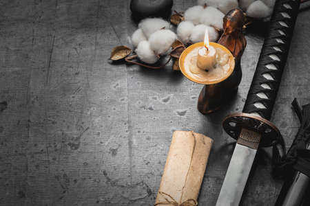 Katana sword, paper scroll and burning candle on the black table background with copy space.