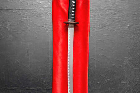 Katana sword on the red cloth on the black table flat lay background.