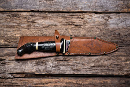Hunting knife and leather case on the old wooden table background. Hunter accessory concept background.