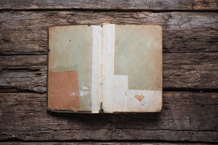 Open old book on the wooden desk table flat lay background.