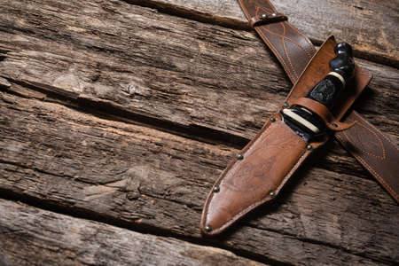 Hunting knife and leather case on the old wooden table background. Hunter accessory concept background with copy space.
