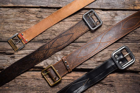 Old retro style male belts on the wooden table flat lay background.