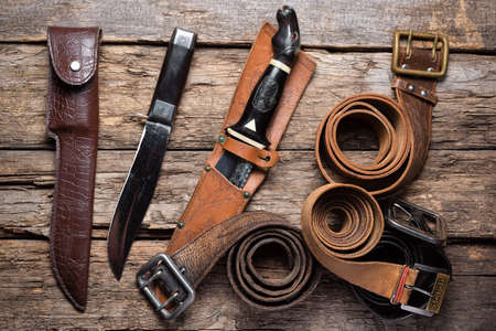 Hunting knives, leather belts and sheaths on the old wooden table background. Hunting concept background.