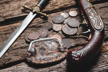 Pirate weapon and ancient coins on the old wooden table background. Piracy. 版權商用圖片