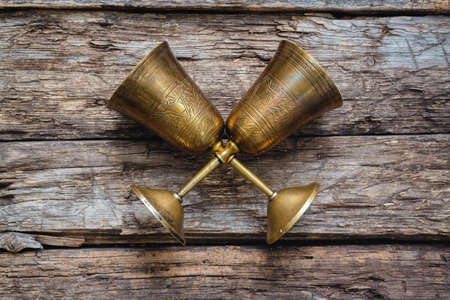 Golden goblets on the old wooden table background. Royal drink concept.