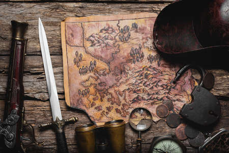 Old treasure map, coins, compass, weapon and pirate hat on the old wooden table flat lay background. 版權商用圖片