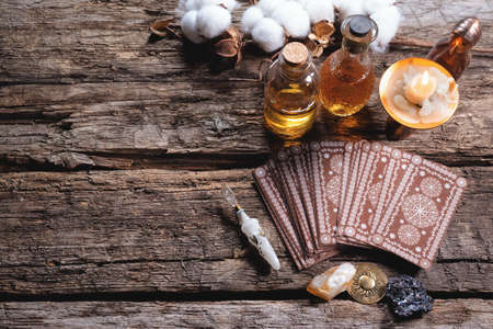Tarot cards and magic potions on the wooden table background. Future reading concept.