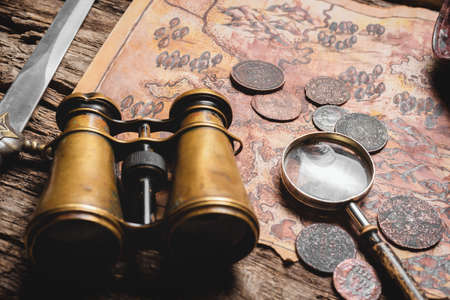 Pirate treasure map, binoculars and magnifying glass on the old wooden table background close up.