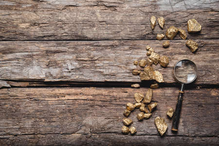 Golden ore and magnifying glass on the old wooden table flat lay background with copy space. Golden mine concept.