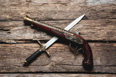 Pirate weapon on the old wooden table background. Piracy. 版權商用圖片