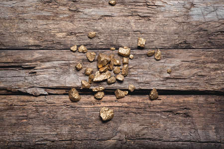 Golden ore on the old wooden table flat lay background. Golden mine concept. 版權商用圖片