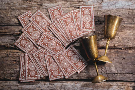 Tarot cards and golden goblets on the wooden flat flat lay background. 版權商用圖片