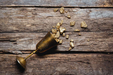 Golden goblet full of gold ore on the old wooden table flat lay background. Wealth concept.