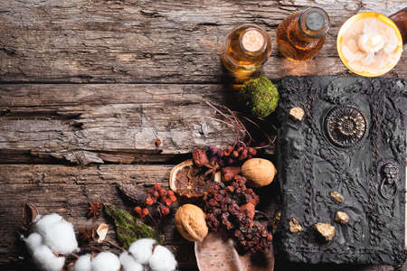 Witchcraft concept background with copy space. Witch doctor. Spell book, magic potions and dried plant on the wooden table.