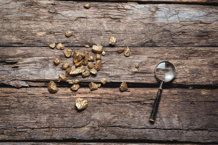 Golden ore and magnifying glass on the old wooden table flat lay background. Golden mine concept. 版權商用圖片