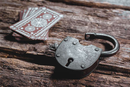 Tarot cards and old padlock on the wooden table background. Hidden future. 版權商用圖片