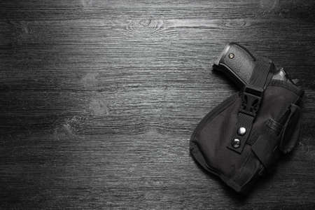 Airsoft gun in the holster on the black flat lay background with copy space.